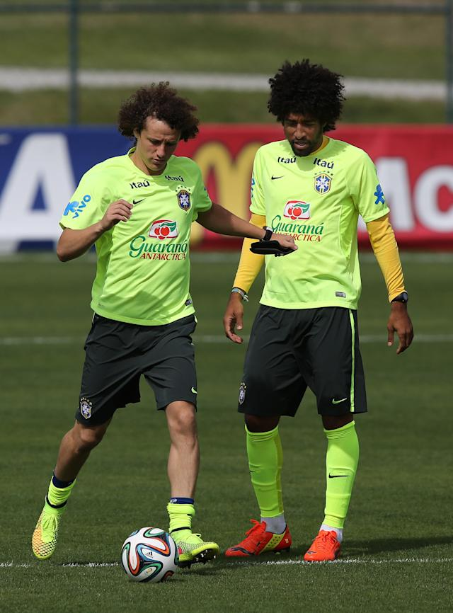 Brazil's David Luiz, left, runs with the ball, as Dante looks on during a practice session at the Granja Comary training center, in Teresopolis, Brazil, Monday, July 7, 2014. Brazil will face Germany on Tuesday in a World Cup semifinal match without Neymar. (AP Photo/Leo Correa)