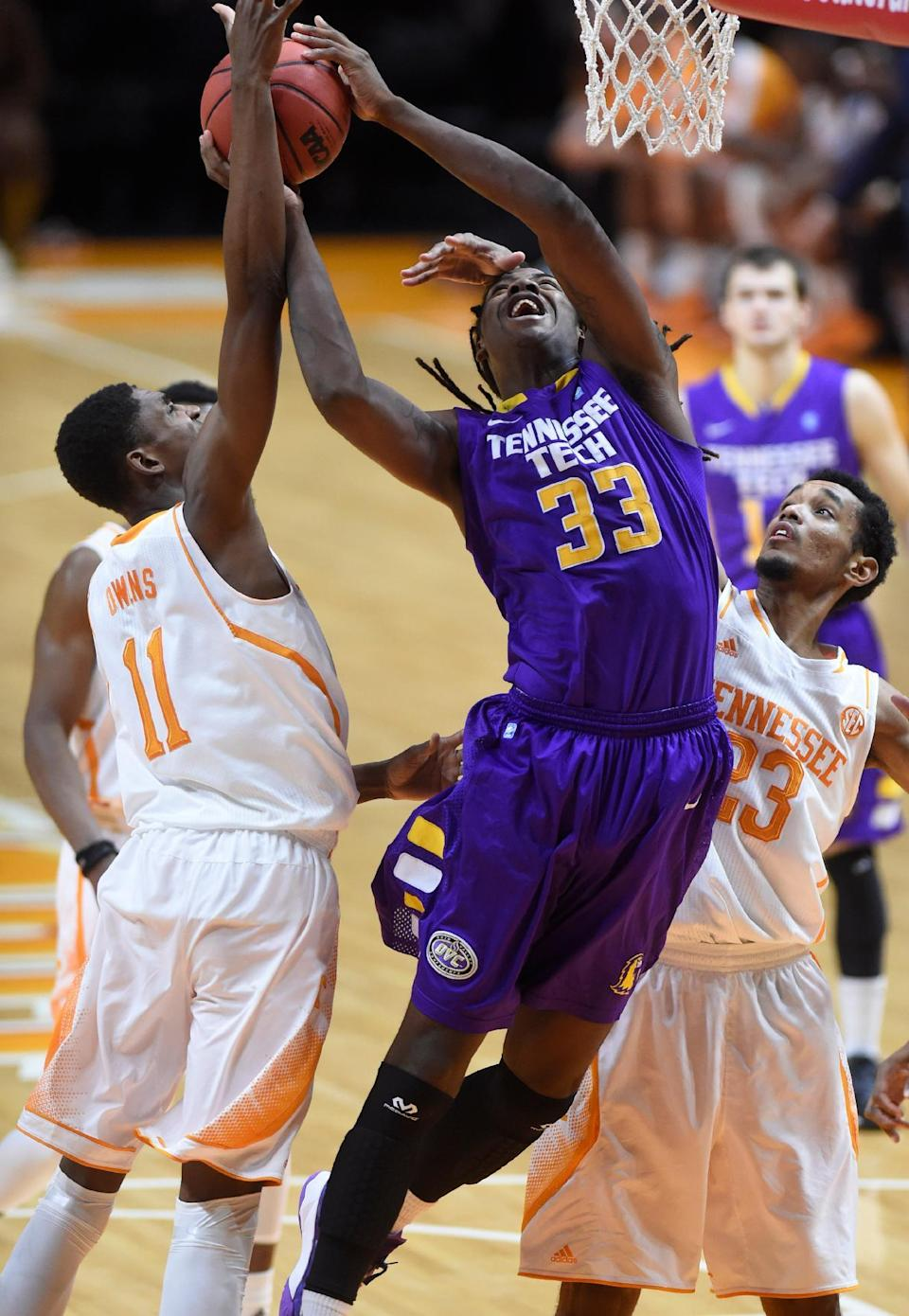 Tennessee forward Tariq Owens (11) blocks a layup by Tennessee Tech forward Dennis Ogbe (33) during the second half of an NCAA college basketball game in Knoxville, Tenn., on Friday, Dec. 19, 2014. (AP Photo/Knoxville News Sentinel, Adam Lau)