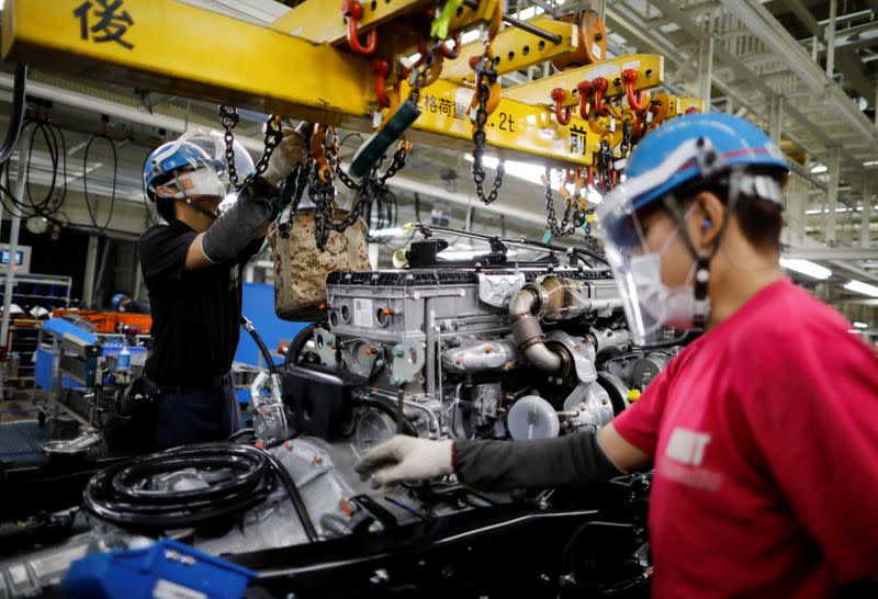 Employees wearing protective face masks and face guards work on the automobile assembly line during the outbreak of the coronavirus disease (COVID-19) at the Kawasaki factory of Mitsubishi Fuso Truck and Bus Corp. in Kawasaki, Japan