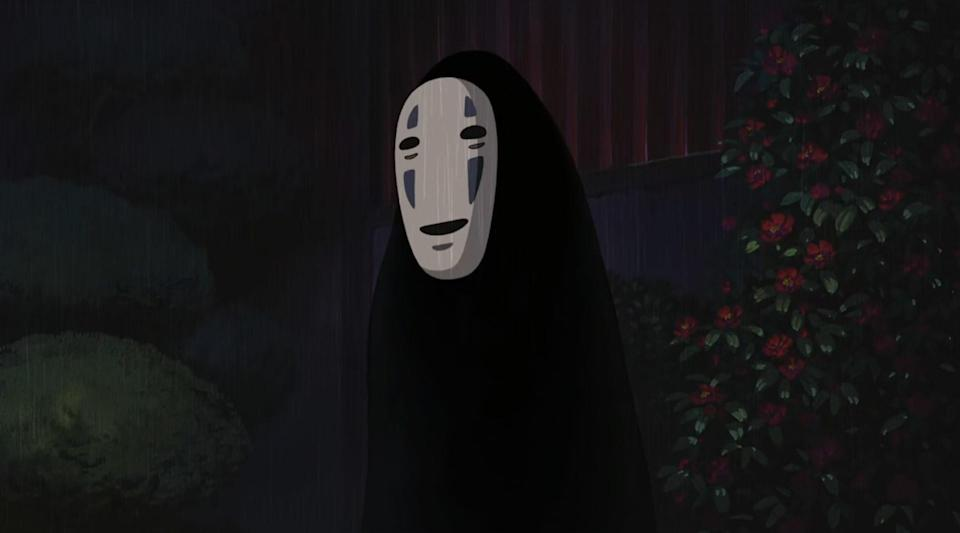 A black humanoid figure with no visible arms and legs wearing a mask that has two eyes and a mouth painted on it.