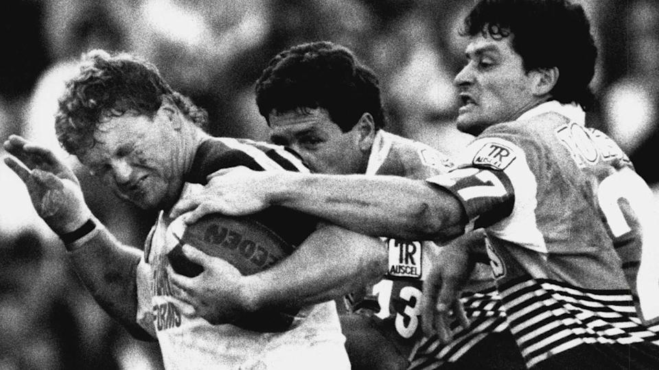 Brad Izzard, pictured here being tackled by Gene Miles and Peter Jackson in 1990.