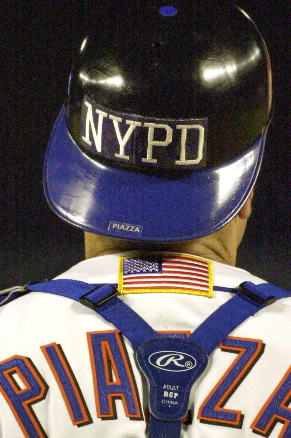 FILE - In this Sept. 21, 2001, file photo, New York Mets catcher Mike Piazza wears the NYPD logo on his helmet as he takes the field in the top of the fifth inning against the Atlanta Braves in New York. Sports teams will hold ceremonies Saturday, Sept.11, 2021, to mark the 20th anniversary of the Sept. 11 terrorist attacks. (AP Photo/Mark Lennihan, File)