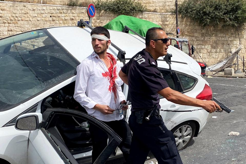 An Israeli policeman stands in front of an injured Israeli driver, moments after witnesses said a car crashed into a Palestinian on a pavementReuters