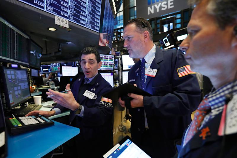 Specialist Peter Mazza, left, and trader Jonathan Corpina, center, work on the floor of the New York Stock Exchange, Friday, April 12, 2019. U.S. stocks moved broadly higher in early trading Friday on Wall Street, putting the market on track for gains at the end of a shaky week. (AP Photo/Richard Drew)