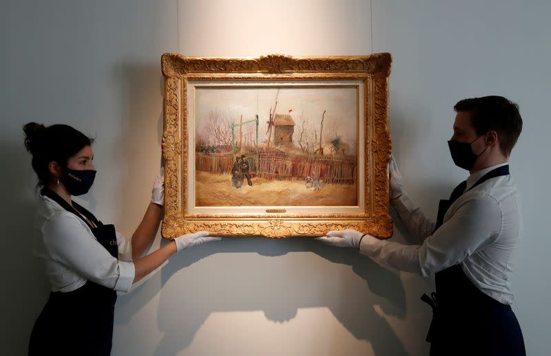 "FILE PHOTO: Sotheby's Paris employees pose with the painting ""Scene de rue a Montmartre"" by Dutch painter Vincent Van Gogh"