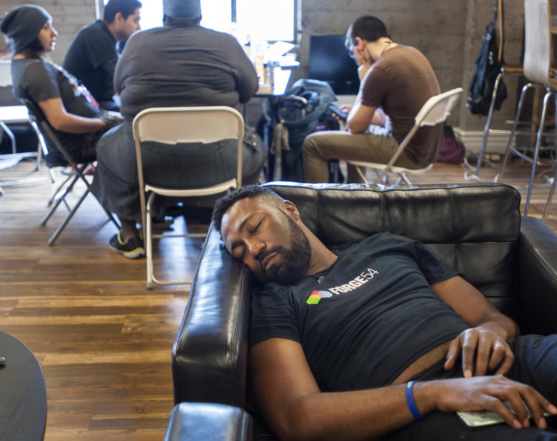 SANTA ANA, CA - OCTOBER 15: Jelani Warren catches some sleep after a late night volunteering with Forge54 while while others work around him. A group of about 100 professionals and students are donating 54 straight hours of their time to help the nonprofit Illumination Foundation in Santa Ana on Saturday, October 15, 2016. They are creating mobile apps, video, graphics and other multiple media for the foundation that helps the homeless in Orange County. (Photo by Mindy Schauer/Digital First Media/Orange County Register via Getty Images)