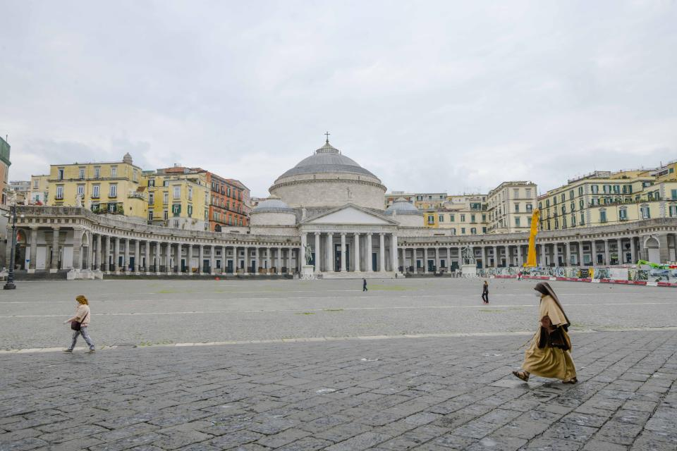A nun walks in an empty Piazza del Plebiscito in Naples, southern Italy, on the first day after being declared a red zone, Sunday, Nov. 15, 2020. The regions of Italy that include the cities of Naples and Florence were declared coronavirus red zones, the latest signals of the dire condition of Italian hospitals struggling with a surge of new admissions. (Alessandro Pone/LaPresse via AP)