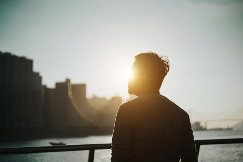 Silhouette of young man standing against urban cityscape and harbour looking up to sky in deep thought