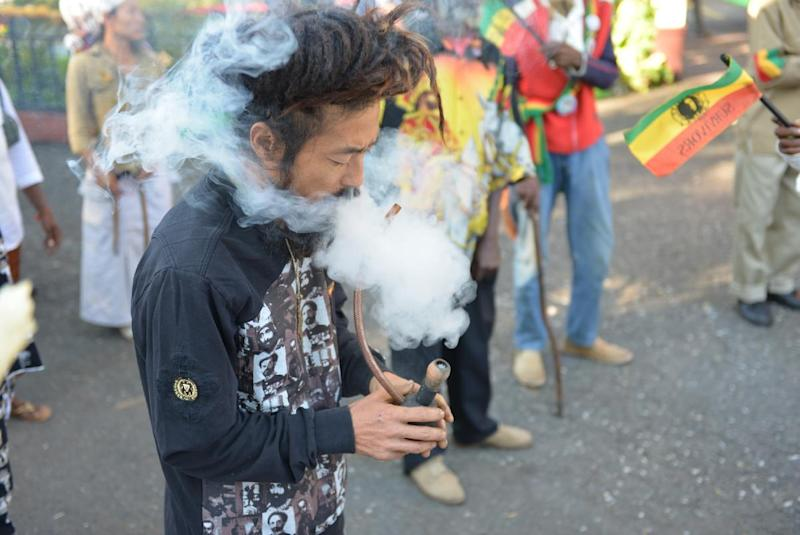 """FILE - In this Feb. 6, 2013 photo, a Rastafarian named Bongho Jatusy smokes a pipe of marijuana outside a museum dedicated to the memory of late reggae icon Bob Marley in Kingston, Jamaica. While marijuana is still illegal in Jamaica, where it is known popularly as """"ganja,"""" increasingly vocal advocates say that Jamaica could give its struggling economy a boost by taking advantage of the fact the island is nearly as famous for its marijuana as it is for beaches, reggae music and world-beating sprinters. Anxiety over U.S. reprisals has always doused reform efforts in Jamaica, including a broadly supported 2001 attempt to approve private use of marijuana by adults. (AP Photo/David McFadden, File)"""