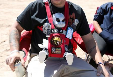 A man wears an alien baby doll as an influx of tourists responding to a call to 'storm' Area 51, a secretive U.S. military base believed by UFO enthusiasts to hold government secrets about extra-terrestrials, is expected in Rachel, Nevada