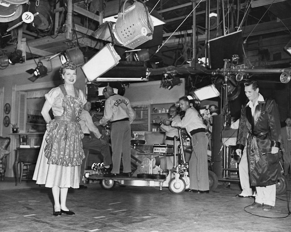 """<p><em>I Love Lucy </em>was <a href=""""https://www.mediavillage.com/article/historys-moments-in-media-launching-a-legend-with-i-love-lucy/#:~:text=So%2C%20Arnaz%20brought%20in%20a,and%20Arnaz%20invented%20the%20sitcom."""" rel=""""nofollow noopener"""" target=""""_blank"""" data-ylk=""""slk:the first show"""" class=""""link rapid-noclick-resp"""">the first show</a> filmed on 35-millimeter film in front of a live studio audience<em>. </em>Here, the couple arrives on set in costume to warm up the studio audience before they begin taping.</p>"""