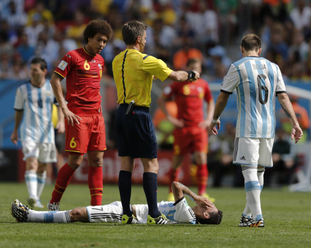 Argentina's Angel di Maria lies on the ground injured as referee Nicola Rizzoli from Italy requests a stretcher to take him off the pitch during the World Cup quarterfinal soccer match between Argentina and Belgium at the Estadio Nacional in Brasilia, Brazil, Saturday, July 5, 2014. At left is Belgium's Axel Witsel and at right, Argentina's Lucas Biglia.(AP Photo/Eraldo Peres)