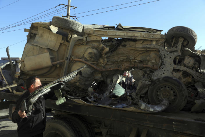 Afghan security watches the removal of a damaged vehicle after a roadside bomb attack in Kabul, Afghanistan, Tuesday, Dec. 22, 2020. A roadside bomb tore through a vehicle in the Afghan capital of Kabul Tuesday, killing multiple people, police said. (AP Photo/Rahmat Gul)