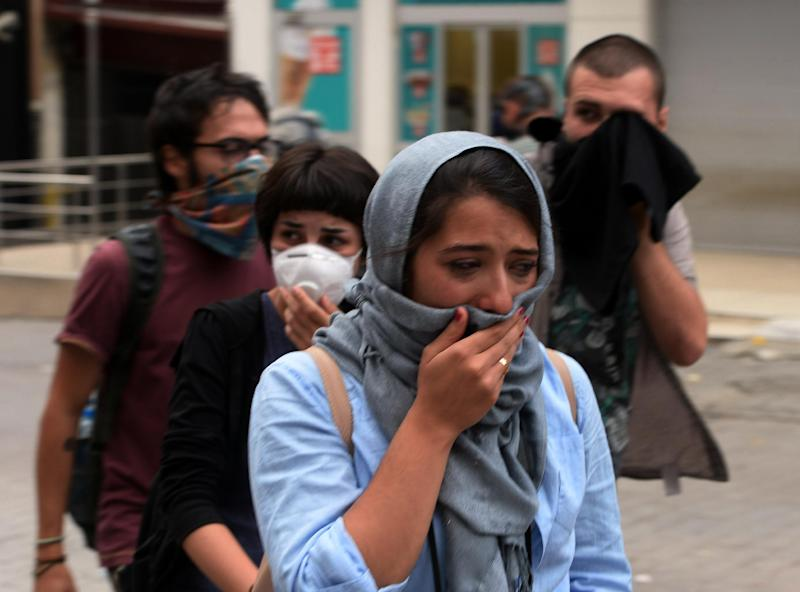People affected by tear gas as riot police use water cannons and tear gas to disperse protesters in Turkish capital, Ankara, late Wednesday, June 5, 2013. In Ankara and Istanbul, thousands of union members asked Turkey's prime minister Recep Tayyip Erdogan to resign.(AP Photo)