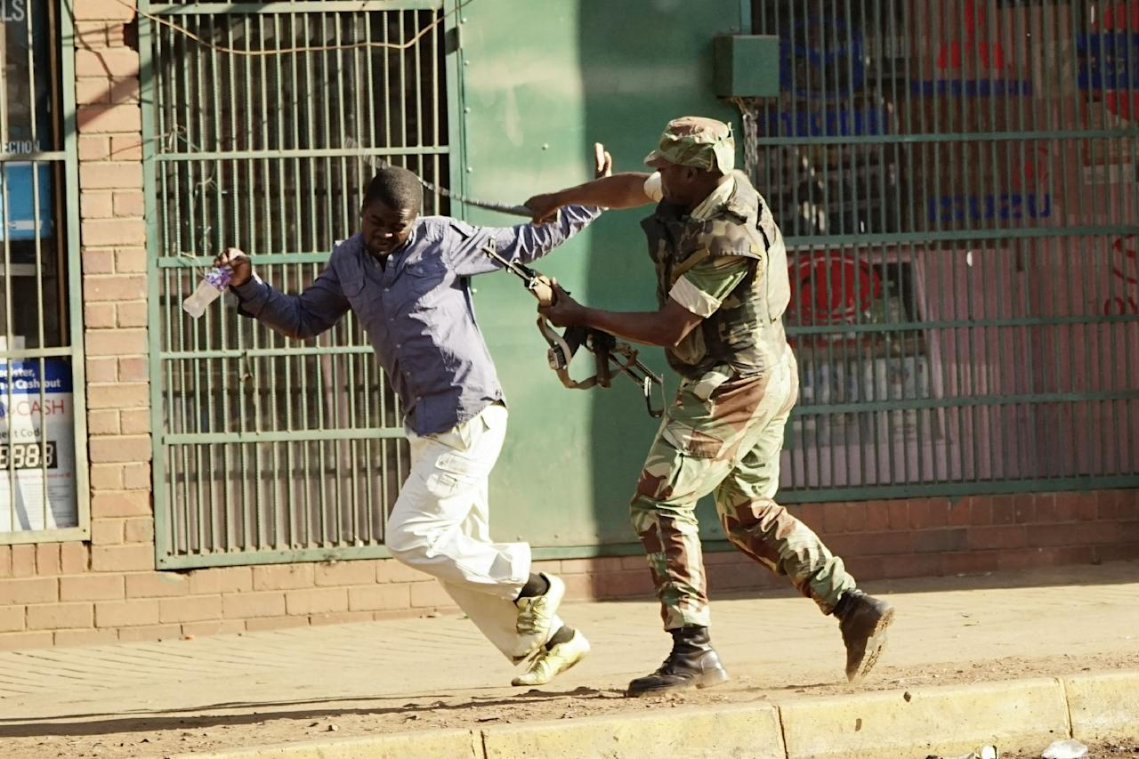 <p>A Zimbabwean soldier beats a man in a street of Harare on August 1, 2018 as protests erupted over alleged fraud in the country's election. – One man was shot dead, AFP witnessed, after the Zimbabwean army opened fire in central Harare on Wednesday as protests erupted over alleged fraud in the country's election. President Emmerson Mnangagwa on August 1 called for peace as police fired water cannon and teargas at opposition supporters in Harare over alleged fraud in Zimbabwe's elections. (Photo: Zinyange Auntony/AFP/Getty Images) </p>