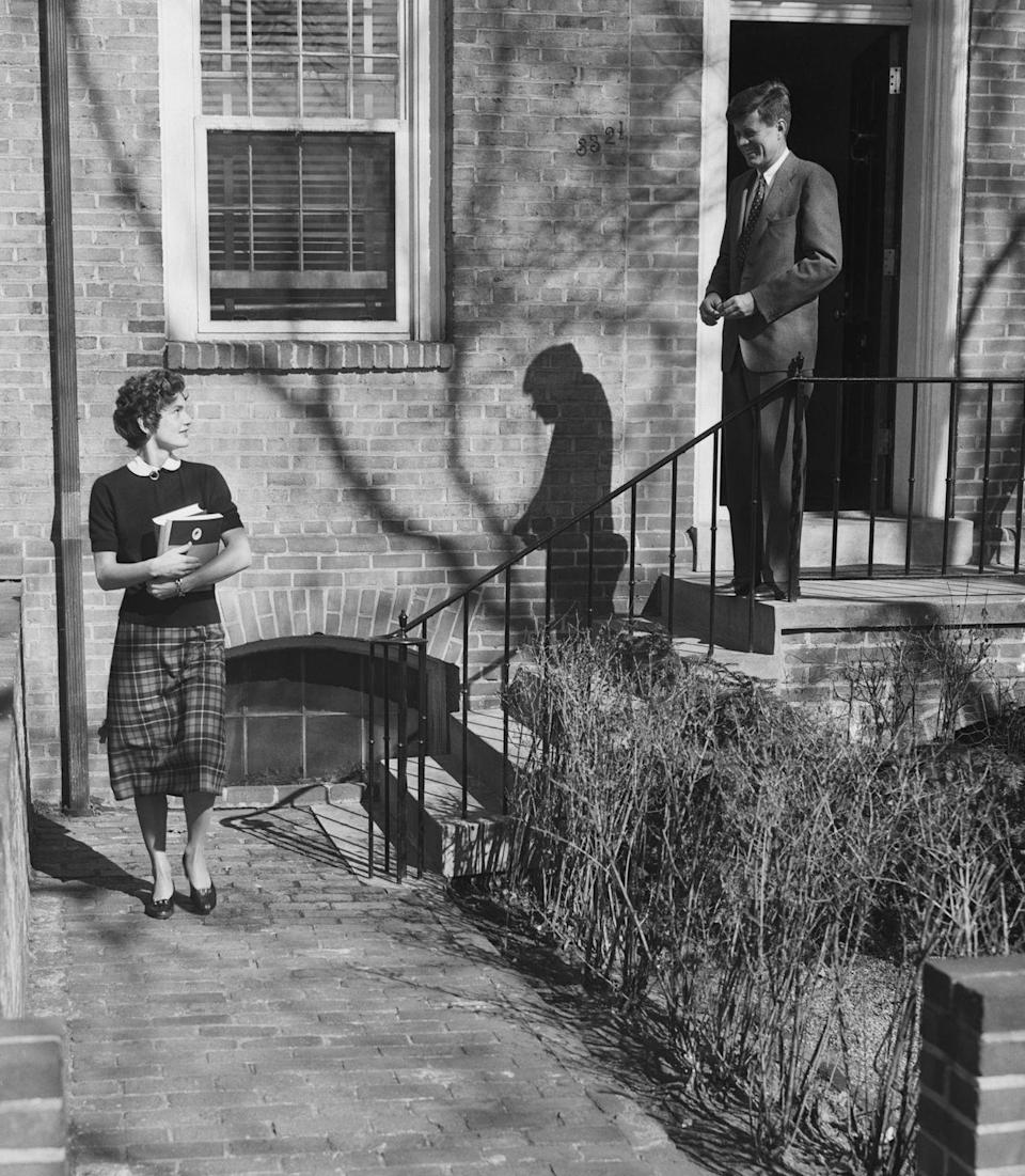 <p>JFK says goodbye to Jackie as she leaves their Washington D.C. townhouse to attend classes at the Georgetown University Foreign Service School. The newlyweds relocated to the nation's capitol for John's term as senator. </p>