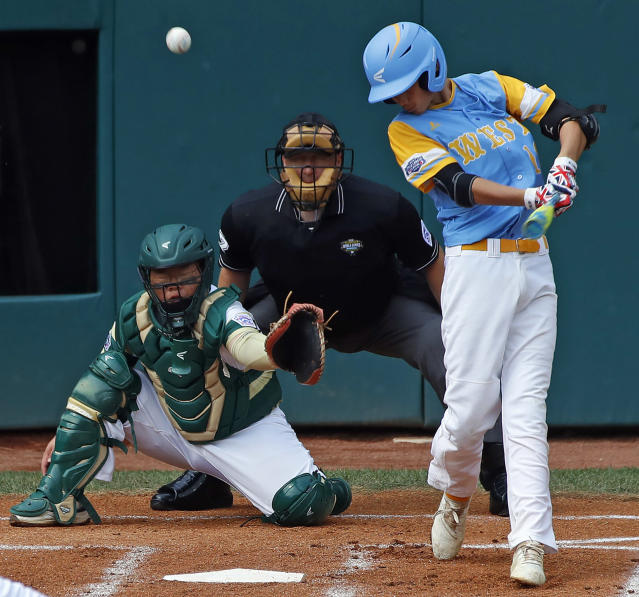 Honolulu, Hawaii's Mana Lau Kong, right, hits the first pitch of the baseball game from South Korea's Yeong Hyeon Kim for a solo home run in the first inning of the Little League World Series Championship in South Williamsport, Pa., Sunday, Aug. 26, 2018. (AP Photo/Tom E. Puskar).