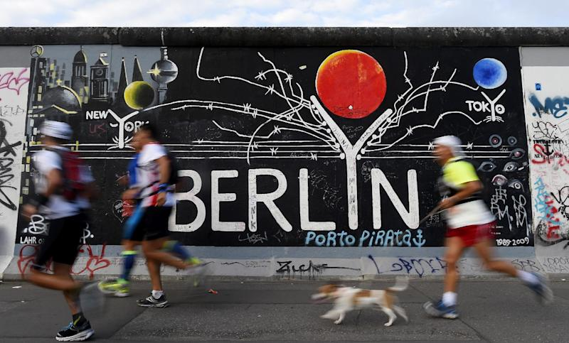 Runners pass the former Berlin Wall during the 160-kilometre (100-mile) ultramarathon event in the German capital on August 16, 2014