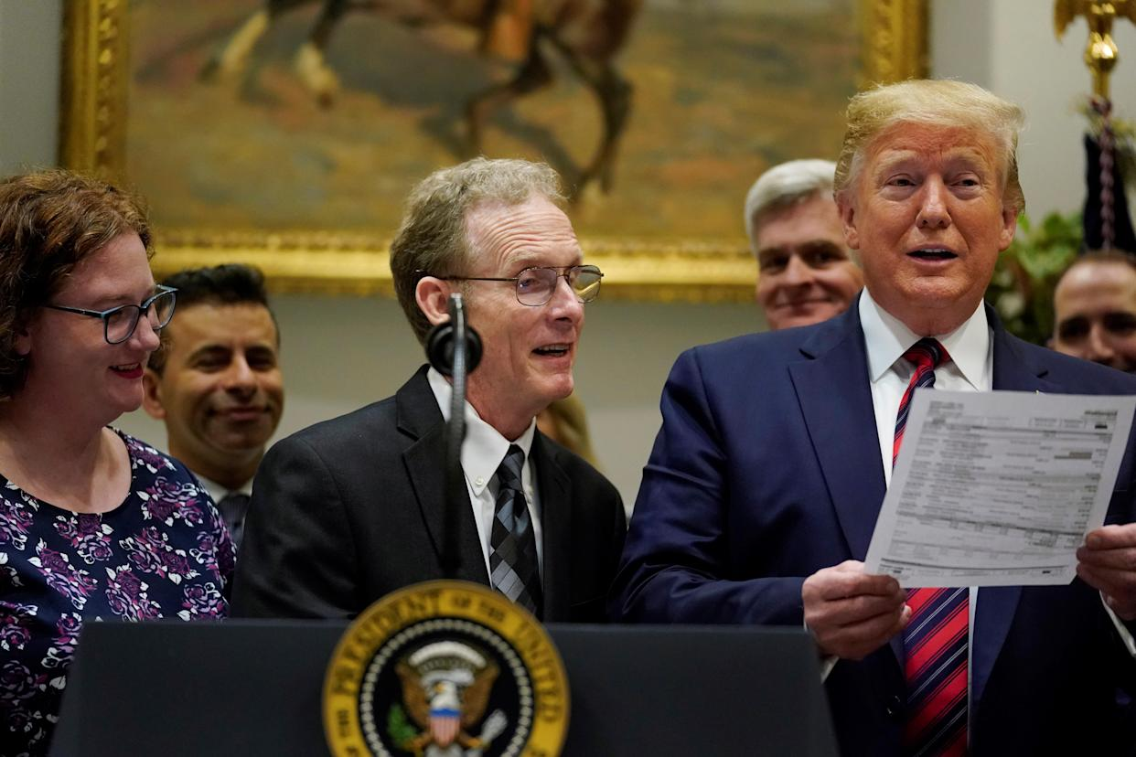 Dr. Paul Davis of Findlay, Ohio, shows U.S. President Donald Trump a surprise $17,000 medical bill his daughter received for a routine test, while Trump spoke to reporters about his support for proposed legislation to curb surprise medical bills at the White House in Washington, U.S. May 9, 2019.  REUTERS/Jonathan Ernst