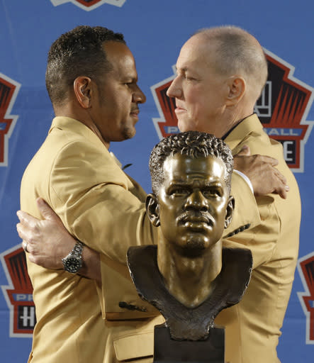 Hall of Fame inductee Andre Reed, left, and former Buffalo Bills quarterback Jim Kelly hug during the Pro Football Hall of Fame enshrinement ceremony Saturday, Aug. 2, 2014, in Canton, Ohio. (AP Photo/Tony Dejak)