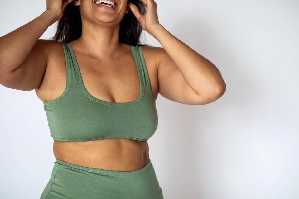 Cropped shot of a chubby woman in underwear on white background. Oversized woman wearing lingerie smiling.