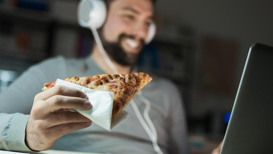man eating pizza with headphones on computer