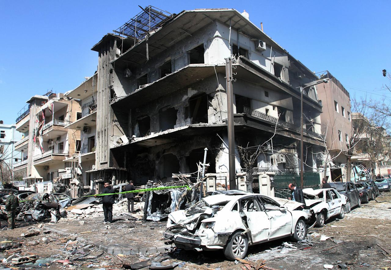 Syrian security officers investigate a damaged building near the aviation intelligence department, which was attacked by one of two explosions, in Damascus, Syria, on Saturday, March 17, 2012. Twin bombings struck government targets in the Syrian capital early Saturday, killing security forces and civilians and leaving pools of blood and carnage in the streets, according to state-run television. (AP Photo/Bassem Tellawi)