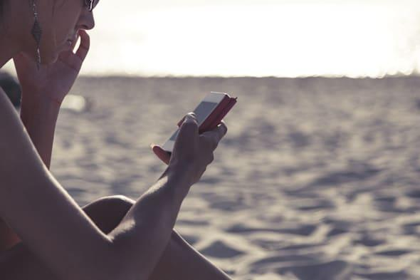 young girl on the beach, typing os smartphone