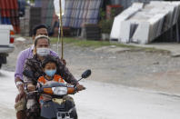 A child receives treatment from an IV drip bottle held by his father as they ride to a nearby clinic along a flooded road following recent rains in Sre Ampel, Cambodia, outside Phnom Penh, on Monday, Sept. 20, 2021. (AP Photo/Heng Sinith)