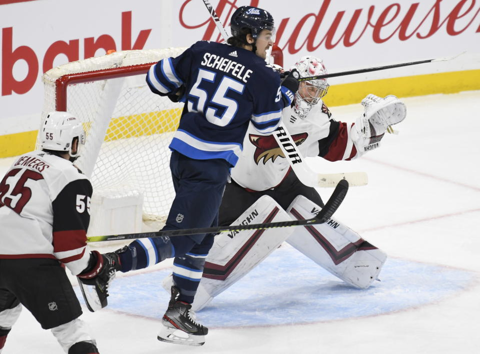 Winnipeg Jets' Mark Scheifele (55) runs into Arizona Coyotes goaltender Darcy Kuemper (35) during the first period of an NHL hockey game Tuesday, Oct. 15, 2019, in Winnipeg, Manitoba. (Fred Greenslade/The Canadian Press via AP)