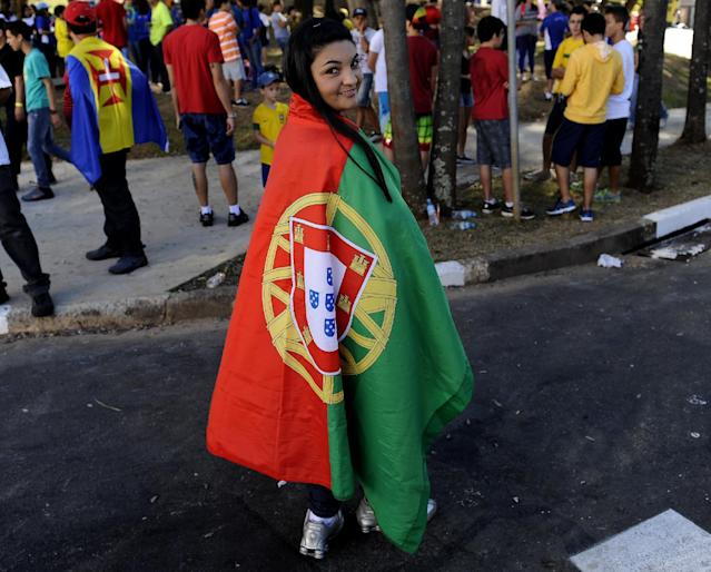 A soccer fan holding a Portuguese flag poses for a photo prior to her entrance to the stadium for a training session of Portugal in Campinas, Brazil, Wednesday, June 18, 2014. Portugal plays in group G of the Brazil 2014 soccer World Cup. (AP Photo/Paulo Duarte)
