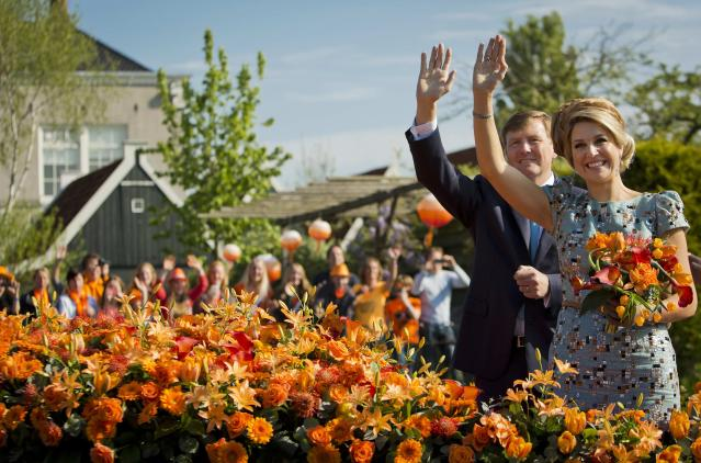 King Willem-Alexander of the Netherlands and his wife Queen Maxima wave during their first King's Day in De Rijp