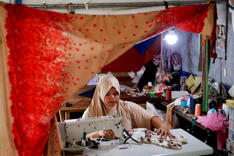 Asnia Muloc Sandiman, 25, works with a sewing machine provided by the government in her family's tent at an evacuation camp for families displaced by the Marawi siege, in Marawi City, Lanao del Sur province, Philippines. (Photo: Eloisa Lopez/Reuters)