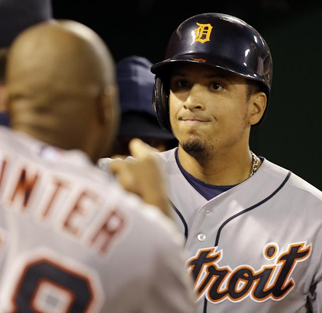 Detroit Tigers Victor Martinez, right, celebrates with teammate Torii Hunter after scoring in the sixth inning of Game 5 of an American League baseball division series against the Oakland Athletics in Oakland, Calif., Thursday, Oct. 10, 2013. (AP Photo/Ben Margot)