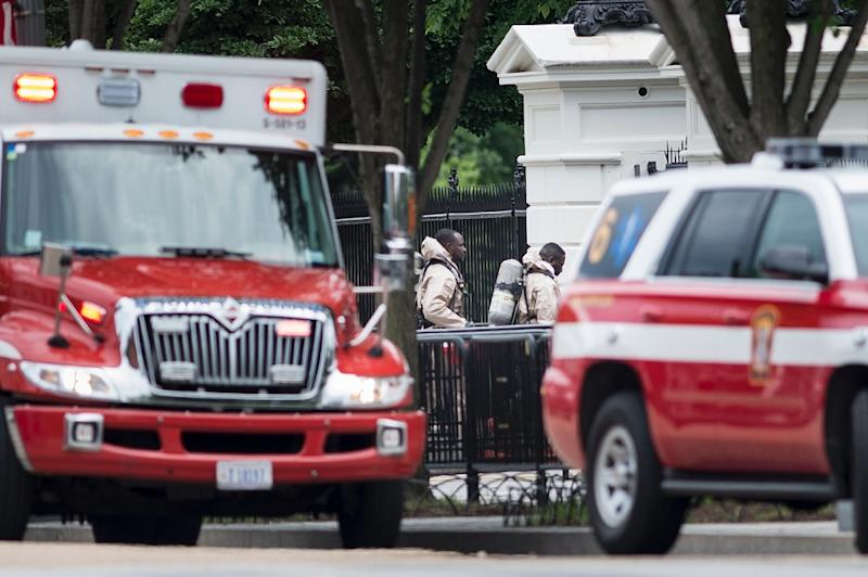 Emergency personnel in protective suits walk to the Northeast gate to the White House from Pennsylvania Avenue during a security lockdown of the White House grounds in Washington, DC