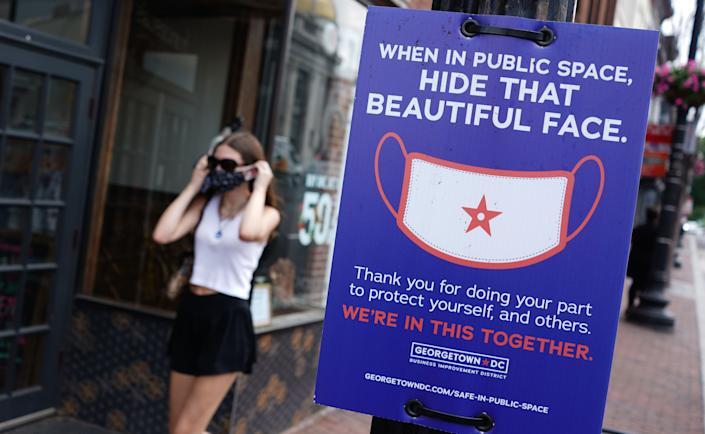 A pedestrian passes by a sign requesting people to wear face coverings in the Georgetown district of Washington, DC on June 22, 2020.  (Mandel Ngan/AFP via Getty Images)