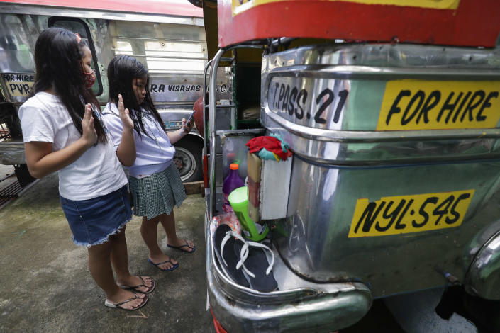"""Grade school students Bhea Joy Roxas, right, and Elrich Joy, left, use a smart phone as they raise their hands while reciting the """"Panatang Makabayan"""" or Patriotic Oath during the opening of classes at the Tandang Sora jeepney terminal in Quezon city, Philippines on Monday, Oct. 5, 2020. Students in the Philippines began classes at home Monday after the coronavirus pandemic forced remote-learning onto an educational system already struggling to fun schools. The two students missed the flag raising ceremony due to poor internet connection. (AP Photo/Aaron Favila)"""