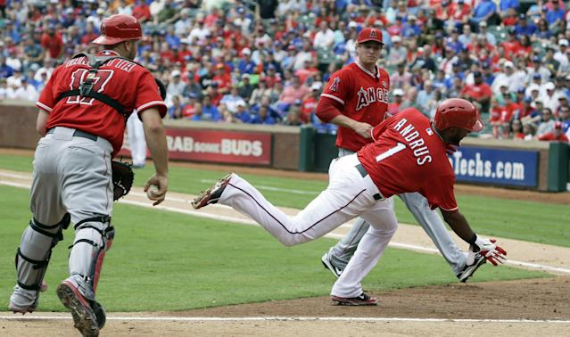 Los Angeles Angels catcher Chris Iannetta (17) and pitcher pitcher Garrett Richards (43) look on as Texas Rangers Elvis Andrus (1) runs in scoring from third base on a wild pitch during the second inning of a baseball game Saturday, Sept. 28, 2013, in Arlington, Texas. (AP Photo/LM Otero)
