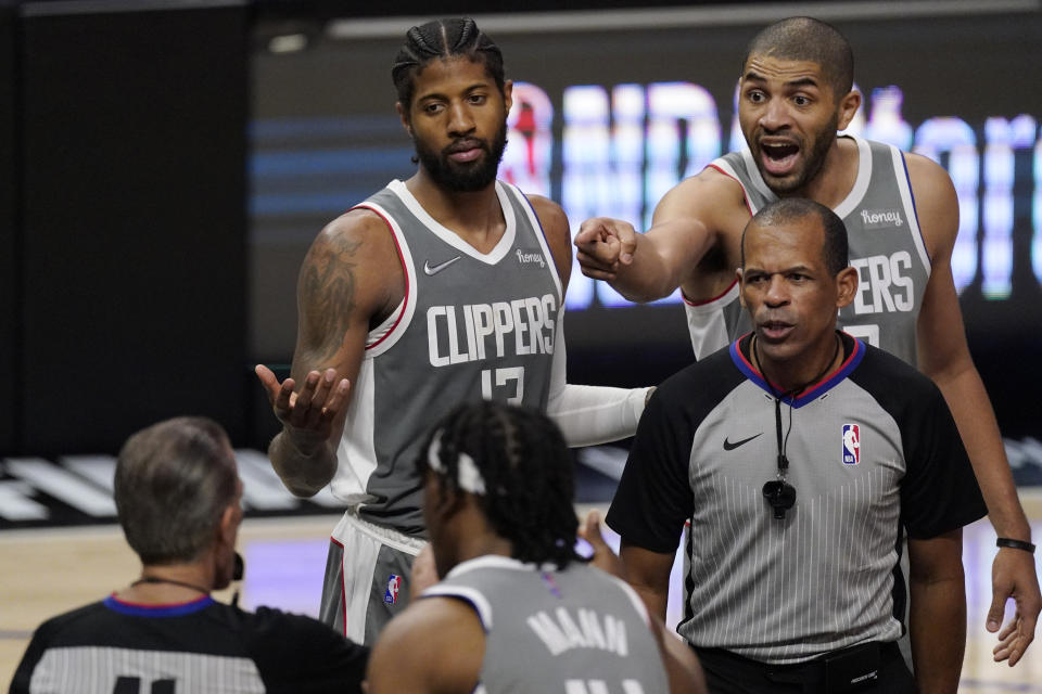 Los Angeles Clippers guard Paul George, left, and forward Nicolas Batum, right, question a foul call during the second half in Game 4 of the NBA basketball Western Conference Finals against the Phoenix Suns Saturday, June 26, 2021, in Los Angeles. (AP Photo/Mark J. Terrill)