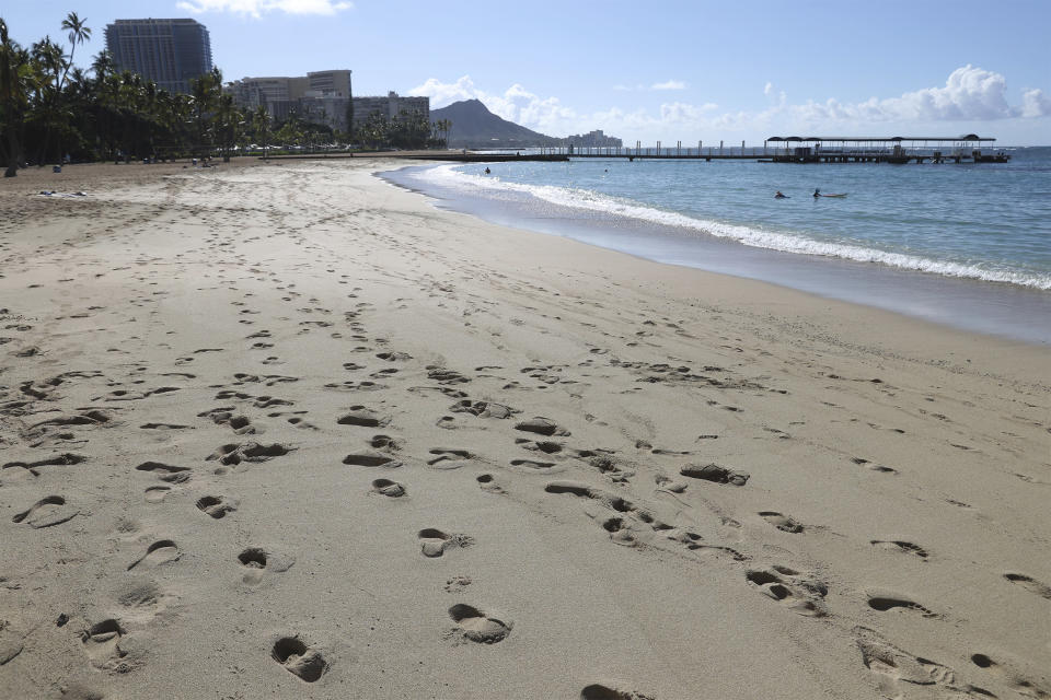 A near empty Waikiki Beach is viewed Thursday, Oct. 15, 2020, in Honolulu. A new pre-travel testing program will allow visitors who test negative for COVID-19 to come to Hawaii and avoid two weeks of mandatory quarantine goes into effect Thursday. The pandemic has caused a devastating downturn on Hawaii's tourism-based economy and many are hoping the testing will help the economy rebound. (AP Photo/Marco Garcia)