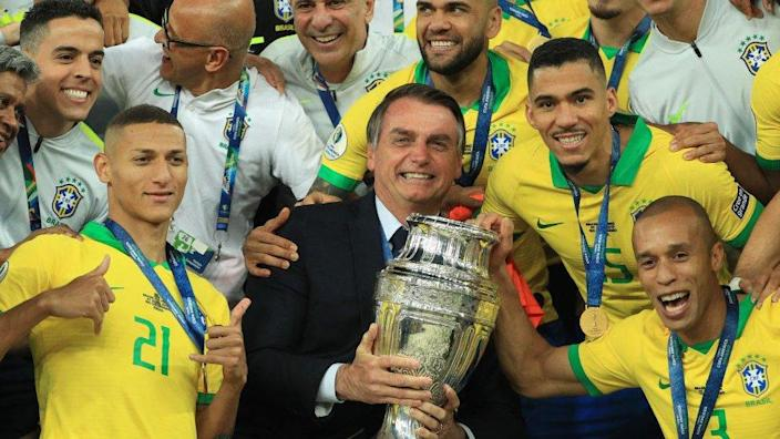 President of Brazil Jair Bolsonaro celebrates with the trophy and the players of Brazil after winning the Copa America Brazil 2019
