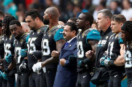 NFL Football - Jacksonville Jaguars vs Baltimore Ravens - NFL International Series - Wembley Stadium, London, Britain - September 24, 2017 Jacksonville Jaguars owner Shahid Khan links arms with players during the national anthems before the match Action Images via Reuters/Paul Childs