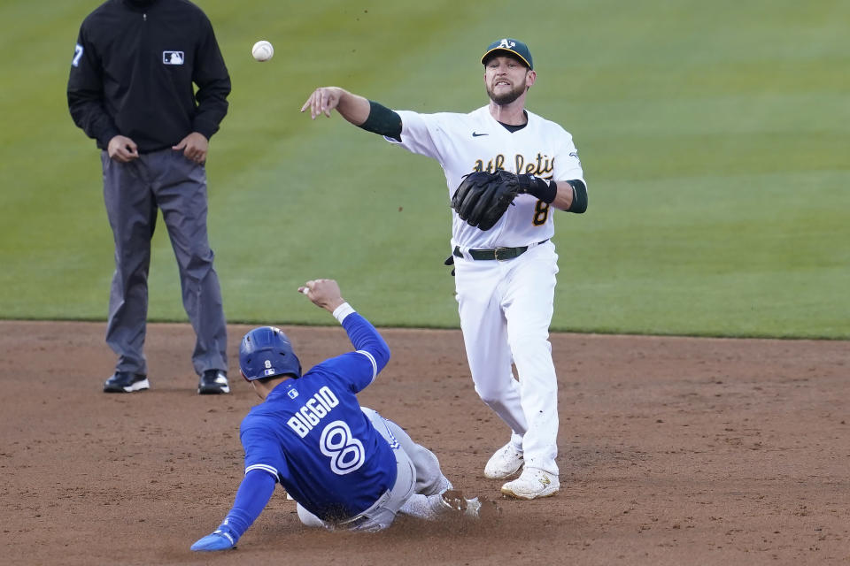 Oakland Athletics second baseman Jed Lowrie, right, throws to first base after forcing out Toronto Blue Jays' Cavan Biggio, bottom, at second base on a double play hit into by Santiago Espinal during the third inning of a baseball game in Oakland, Calif., Tuesday, May 4, 2021. (AP Photo/Jeff Chiu)