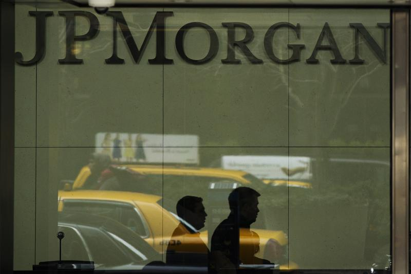 Two men walk past the front desk inside of the headquarters of JPMorgan Chase & Co bank in New York