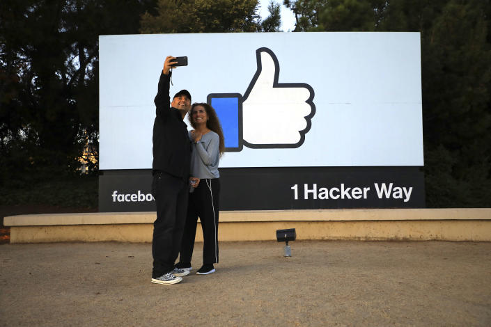 Visitors take a selfie by the Facebook sign at the company