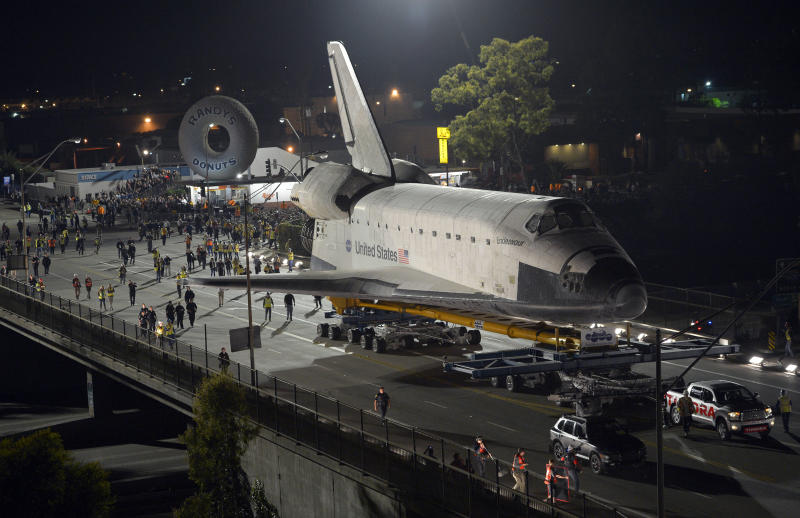 The Space Shuttle Endeavour is slowly moved across Interstate 405 by a Toyota Tundra, Friday, Oct.12, 2012, in Los Angeles. The shuttle is on its last mission — a 12-mile creep through city streets. It will move past an eclectic mix of strip malls, mom-and-pop shops, tidy lawns and faded apartment buildings. Its final destination: California Science Center in South Los Angeles where it will be put on display. (AP Photo/Mark J. Terrill)