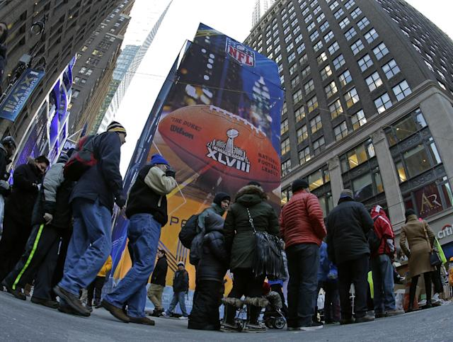 People line up for an attraction during Super Bowl Boulevard activities Wednesday, Jan. 29, 2014, in New York. The Seattle Seahawks are scheduled to play the Denver Broncos in the NFL Super Bowl XLVIII football game on Sunday, Feb. 2, in East Rutherford, N.J. (AP Photo/Charlie Riedel)