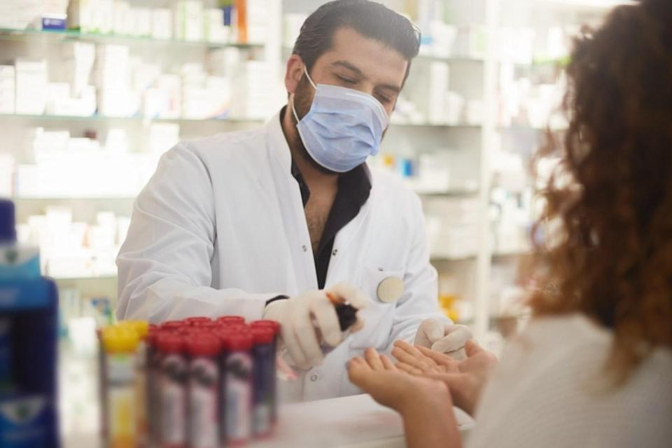 pharmacist squeezes hand sanitizer to the customer