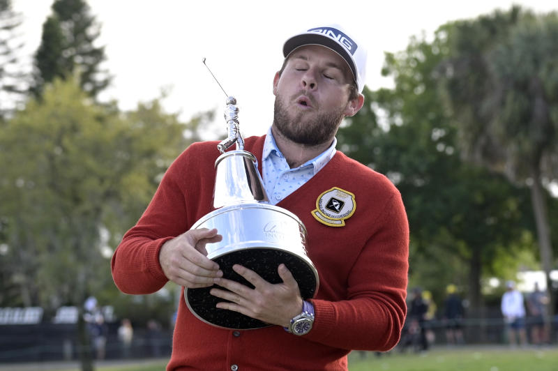 Tyrrell Hatton, of England, reacts to the weight of the championship trophy after posing for photos with it after winning the Arnold Palmer Invitational golf tournament, Sunday, March 8, 2020, in Orlando, Fla. (AP Photo/Phelan M. Ebenhack)