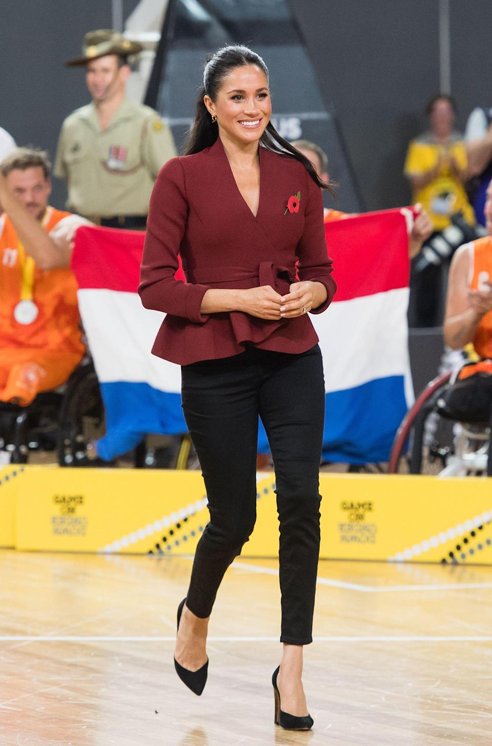 """<p>To watch the US v Netherlands basketball final the pregnant Duchess wore a maroon wrap top with peplum by popular luxury Australian label <a href=""""https://us.scanlantheodore.com/collections/w18-rwt/products/crepeknitwrapjacketgarnet"""" rel=""""nofollow noopener"""" target=""""_blank"""" data-ylk=""""slk:Scanlan Theodore"""" class=""""link rapid-noclick-resp"""">Scanlan Theodore</a>, with black <a href=""""https://outlanddenim.co.uk/collections/women-1/products/harriet-in-black-1"""" rel=""""nofollow noopener"""" target=""""_blank"""" data-ylk=""""slk:Outland jeans"""" class=""""link rapid-noclick-resp"""">Outland jeans</a> and <a href=""""https://www.sarahflint.com/collections/pumps-1/products/jay-pump-100-black-suede?variant=28249886273&clickId=2480597981&clickId=2480597981&publisherId=21181"""" rel=""""nofollow noopener"""" target=""""_blank"""" data-ylk=""""slk:Sarah Flint heels"""" class=""""link rapid-noclick-resp"""">Sarah Flint heels</a>.</p>"""